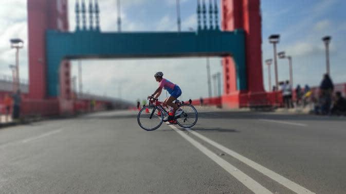 Salah satu peserta wanita di Palembang Triathlon 2020 yang bersepeda melintasi Jembatan Ampera (Liputan6.com / Nefri Inge)