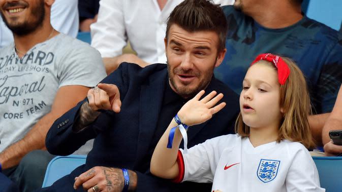 Legenda Timnas Inggris, David Beckham, bersama anak perempuannya, Harper Beckham, saat menyaksikan pertandingan antara Inggris melawan Norwegia pada laga Piala Dunia Wanita di Prancis, (27/6/2019). (Photo by LOIC VENANCE / AFP)