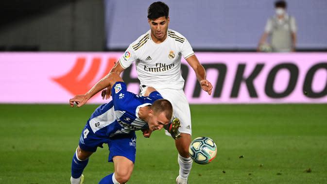 Gelandang Real Madrid, Marco Asensio (kanan) berebut bola dengan bek Alaves, Rodrigo Ely pada lanjutan Liga Spanyol di stadion Alfredo di Stefano, Sabtu (11/7/2020). Real Madrid menang 2-0 lewat gol Karim Benzema dan Marco Asensio. (GABRIEL BOUYS/AFP)