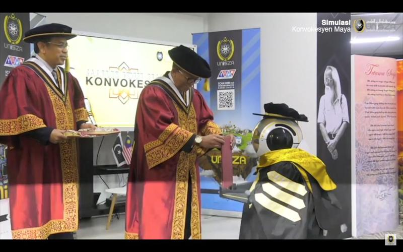 A robot receiving a scroll from UniSZA vice-chancellor Datuk Dr Hassan Basri Awang Mat Dahan (middle). — Screengrab from YouTube/UniSZA Official Channel