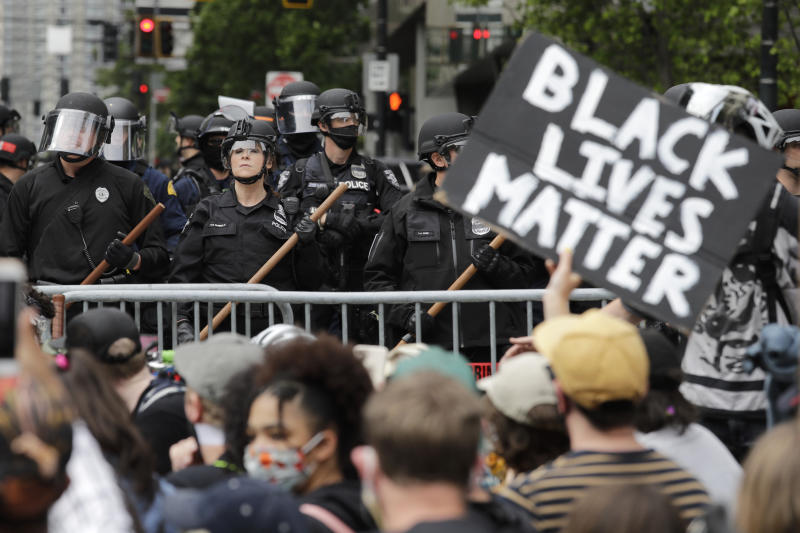 FILE - In this June 3, 2020, file photo, police officers behind a barricade look on as protesters fill the street in front of Seattle City Hall, in Seattle, following protests over the death of George Floyd, a black man who was in police custody in Minneapolis. The King County Labor Council, the largest labor group in the Seattle area, vote Wednesday night June 17 to expell the city's police union, saying the guild representing officers failed to address racism within its ranks. (AP Photo/Elaine Thompson, File)