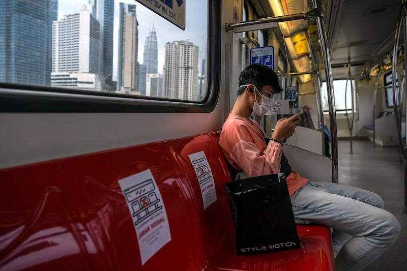 A man looks at his mobile phone during a ride on an LRT in Kuala Lumpur March 24, 2020. — Bernama pic