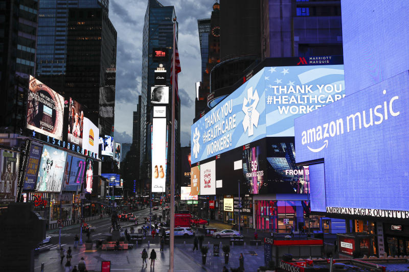 A screen displays a message thanking health care workers during the coronavirus outbreak, in a sparsely populated Times Square, Friday, March 20, 2020, in New York. New York Gov. Andrew Cuomo is ordering all workers in non-essential businesses to stay home and banning non-essential gatherings statewide. (AP Photo/John Minchillo)