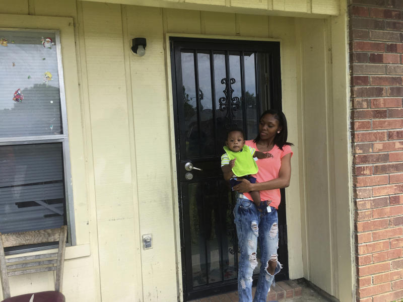 FILE - In this May 9, 2018, file photo, Starr Jones, 21, stands outside her Shelby, Miss., apartment with her 9-month-old son, Jarvis Kemp, after talking with the nonprofit group Save the Children about her community work to fight poverty. A Save the Children report released Tuesday, June 2, 2020, says childhood disparities around malnutrition, graduation rates, and early deaths are worst in the U.S. among rural, black-majority counties in the American South and isolated counties with Native American populations. (AP Photo/Russell Contreras, File)