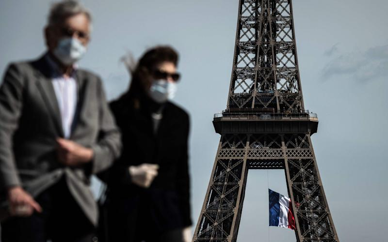 """FILES) In this file photo taken on May 11, 2020, a man and a woman wearing face masks walk on Trocadero Plaza as a French national flag flies on the Eiffel Tower in background in Paris on the first day of France's easing of lockdown measures in place for 55 days to curb the spread of the COVID-19 pandemic, caused by the novel coronavirus. - Wearing a mask will be compulsory in parts of Paris and its wider region from August 10, 2020, to combat a rise in coronavirus infections in and around the French capital, the police said. The mask will be obligatory for all those aged 11 and over from 8:00 am (0600 GMT) on August 10 """"in certain very crowded zones"""", the police said in a statement on August 8, without yet detailing which areas were affected. - PHILIPPE LOPEZ/AFP via Getty Images"""