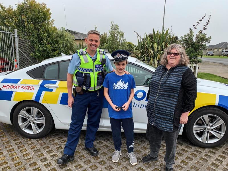 Ryan and his grandmother Kathie with Senior Sergeant Graeme Fleming at Pokeno station.