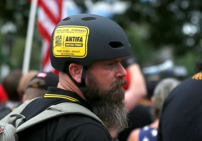 """FILE PHOTO: A man wears a sticker that says """"Antifa Hunting Permit"""" at a Proud Boys rally in Portland, Oregon"""