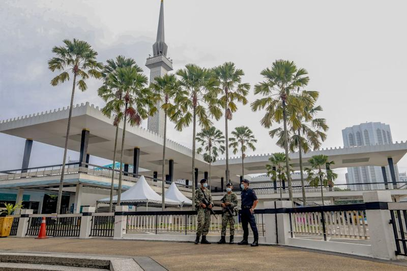 Police and Armed Forces personnel patrol the perimeter of the National Mosque, Kuala Lumpur May 24, 2020 — Picture by Firdaus Latif