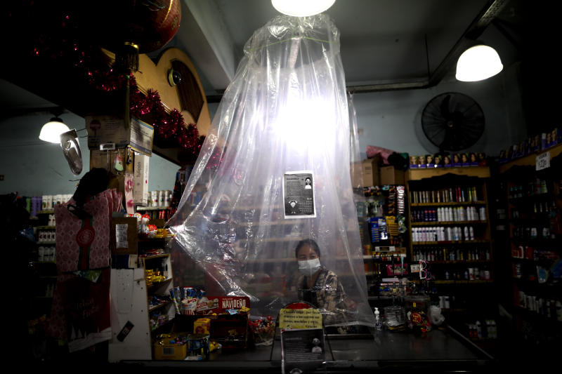FILE - In this March 16, 2020, file photo, supermarket cashier waits for costumers behind a makeshift plastic curtain as a precaution against the spread of the new coronavirus, in Buenos Aires, Argentina. Grocery workers across the globe are working the front lines during lockdowns meant to keep the coronavirus from spreading. (AP Photo/Natacha Pisarenko)