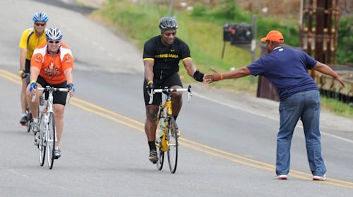 Bo Jackson greets a fan as he pedals to Jack's restaurant in Pleasant Grove, Ala., Friday, April 27, 2012,, on the fourth day of the Bo Bikes Bama charity bike ride on the one-year anniversary of the deadly Alabama tornadoes. Jackson and about 140 bicyclists and the celebrity bikers rode from Cordova, Ala. to Bessemer, Ala. on Friday. (AP Photo/The News, Linda Stelter) MAGS OUT