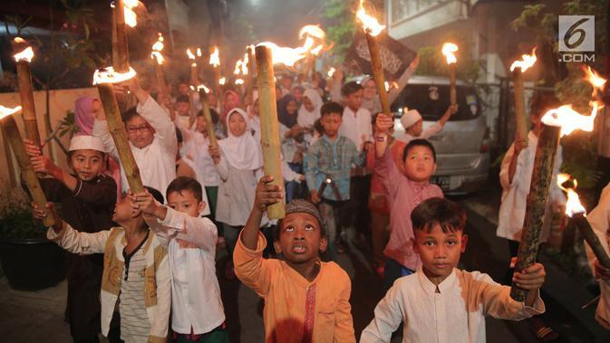 Anak-anak mengikuti pawai obor menyambut Tahun Baru Islam 1 Muharam 1439 Hijriah kawasan Cikini, Jakarta, Rabu (20/9). Tanggal 21 September menjadi awal tahun bagi penanggalan kalender 1439 Hijriah. (Liputan6.com/Faizal Fanani)