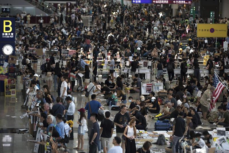 Protesters clog the departure area at Hong Kong's reopened airport Tuesday.