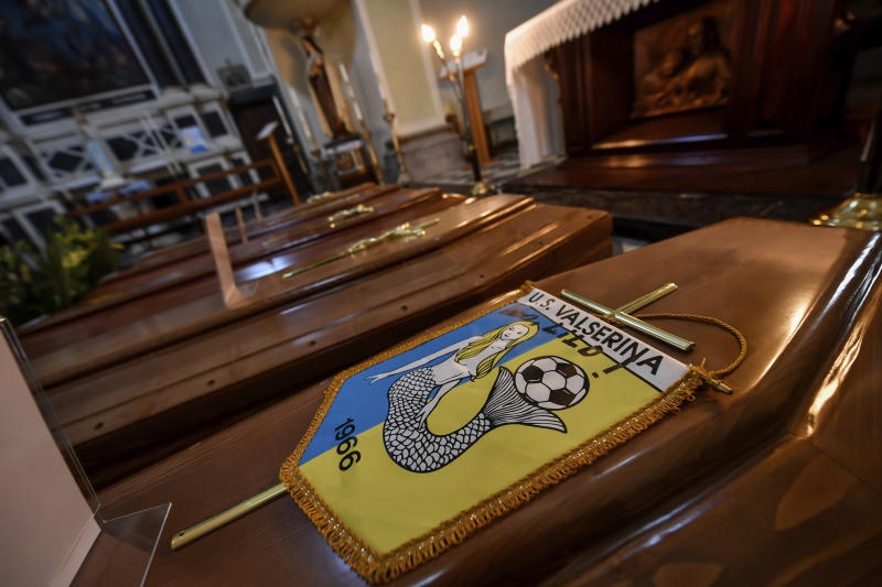 "FILE - In this Saturday, March 21, 202 file photo, coffins, one of them with the pennant of the local soccer team, wait to be transported to cemetery, in the church of Serina, Seriana valley, where many Atalanta fans live, near Bergamo, Northern Italy. It was the biggest soccer game in Atalanta's history and a third of Bergamo's population made the short trip to Milan's famed San Siro Stadium to witness it. Nearly 2,500 fans of visiting Spanish club Valencia also traveled to the Champions League match. More than a month later, experts are pointing to the Feb. 19 game as one of the biggest reasons why Bergamo has become one of the epicenters of the coronavirus pandemic — a ""biological bomb"" was the way one respiratory specialist put it — and why 35% of Valencia's team became infected. The new coronavirus causes mild or moderate symptoms for most people, but for some, especially older adults and people with existing health problems, it can cause more severe illness or death. (Claudio Furlan/LaPresse via AP, File)"
