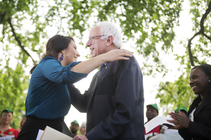 """UNITED STATES - MAY 19: Sen. Bernie Sanders, I-Vt., hugs Alexandra Flores-Quilty, 23, of Oregon, who has $50,000 in student debt, during news conference at the Senate swamp on legislation """"to eliminate undergraduate tuition at public colleges and universities and to expand work-study programs,"""" May 19, 2015. (Photo By Tom Williams/CQ Roll Call)"""