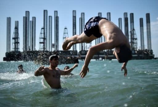 Swimmers in the Caspian Sea near oil rigs in the Azerbaijani capital Baku
