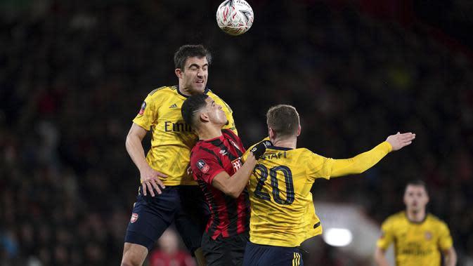 Striker Bournemouth, Dominic Solanke (tengah) berebut bola udara dengan bek Arsenal, Sokratis Papastathopoulos dan Shkodran Mustafi pada pertandingan putaran keempat Piala FA di Stadion Vitalitas, Inggris (27/1/2020). Arsenal berhasil melaju ke babak kelima Piala FA. (John Walton/PA via AP)