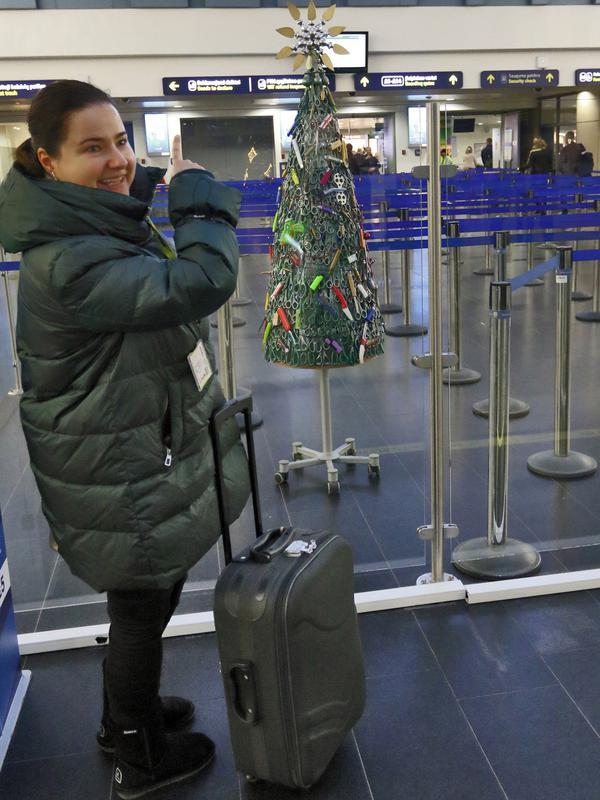 Seorang perempuan mengambil gambar Pohon Natal dari barang-barang sitaan di Bandara Vilnius, Lithuania pada 12 Desember 2019. Bandara Lithuania mengatakan pohon ini dikumpulkan dari barang-barang terlarang yang disita petugas selama proses penyaringan. (Photo by Petras Malukas / AFP)
