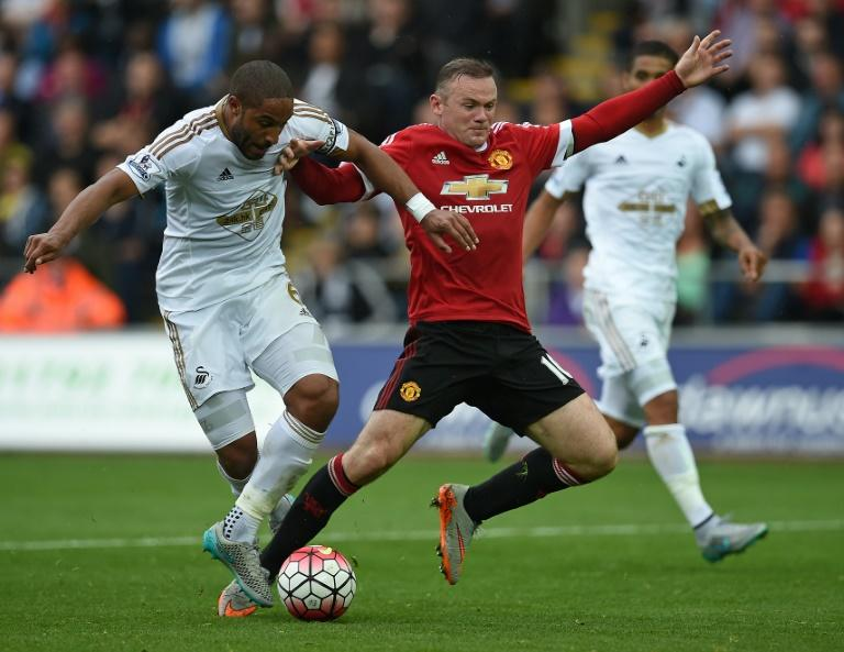 Swansea City's Ashley Williams (L) challenges Manchester United's Wayne Rooney in the penalty area during their Premier League match at The Liberty Stadium in Swansea on August 30, 2015