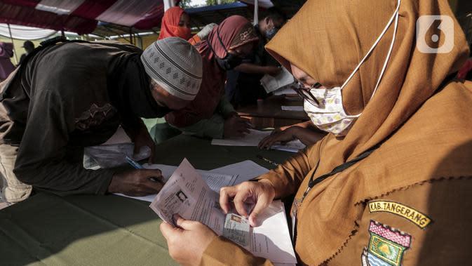 Petugas melayani warga yang antre menerima Bantuan Sosial Tunai (BST) di Desa Cikande, Kecamatan Jayanti, Kabupaten Tangerang, Banten, Selasa (23/6/2020). Bantuan tersebut merupakan salah satu program jaring pengaman sosial terkait pandemi virus corona COVID-19. (Liputan6.com/Johan Tallo)