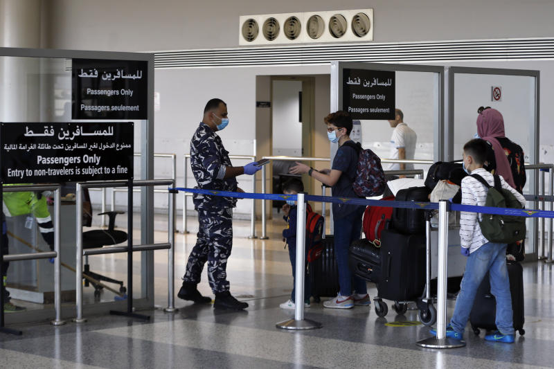 A Lebanese officer checks passports of travelers at the departure terminal of the Rafik Hariri International Airport in Beirut, Lebanon, Wednesday, July 1, 2020. Beirut's airport is partially reopening after a three-month shutdown and Lebanon's cash-strapped government is hoping that Thousands of Lebanese expatriates will return for the summer, injecting dollars into the country's sinking economy. (AP Photo/Bilal Hussein)