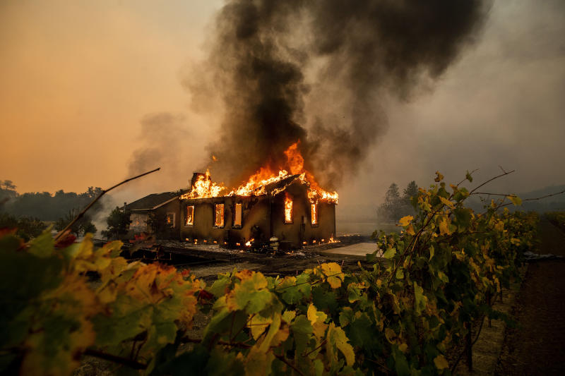 Vines surround a burning building as the Kincade Fire burns through the Jimtown community of unincorporated Sonoma County, Calif., Oct. 24, 2019. (AP Photo/Noah Berger)