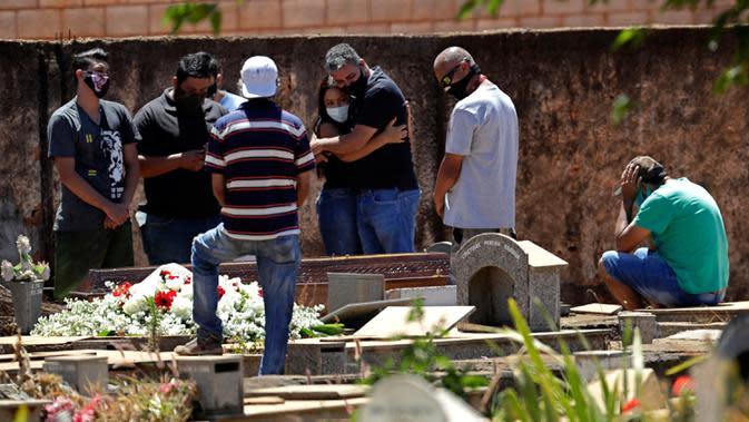 Anggota keluarga menghadiri pemakaman Elvira Maria de Jesus (75), yang dikatakan meninggal karena COVID-19, di pemakaman Campo da Esperanca di Brasilia, Brasil, Kamis (3//9/2020). Brasil melaporkan rata-rata lebih dari 1.000 kematian setiap hari akibat corona sejak akhir Mei. (AP Photo/Eraldo Peres)