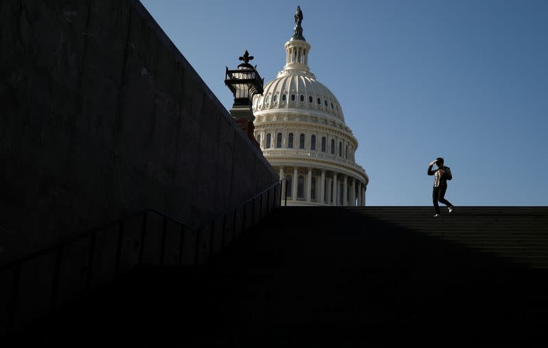A visitor walks outside of the U.S. Capitol before an expected House vote on appointing impeachment managers in Washington
