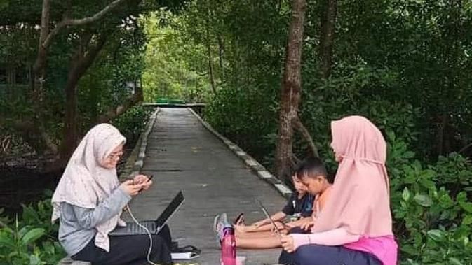 Tak hanya murid, guru di Desa Tani Baru, Kecamatan Anggana, Kabupaten Kutai Kartanegara juga harus berupaya mencari titik dengan kualitas jaring bagus untuk memberikan materi pelajaran daring. (Foto: Istimewa)