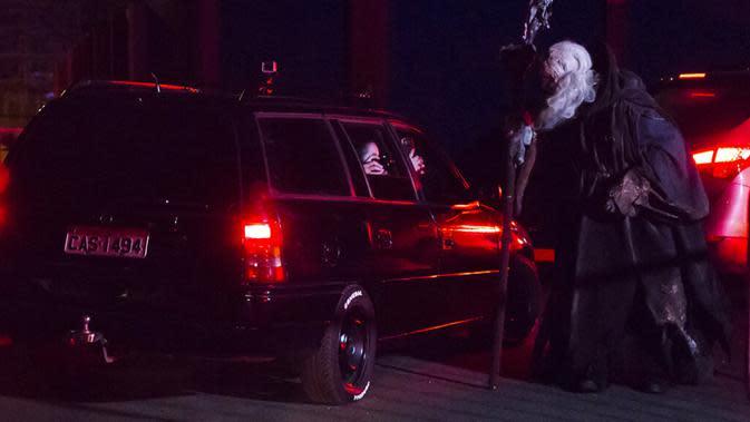 Pengunjung memotret seorang aktor dari dalam mobil mereka di taman hiburan horor Hopi Hari, pinggiran Vinhedo, Sao Paulo, Brasil, Jumat (4/9/2020). Karena pembatasan akibat COVID-19, taman hiburan horor Hopi Hari menampilkan pertunjukan secara drive-thru. (AP Photo/Carla Carniel)