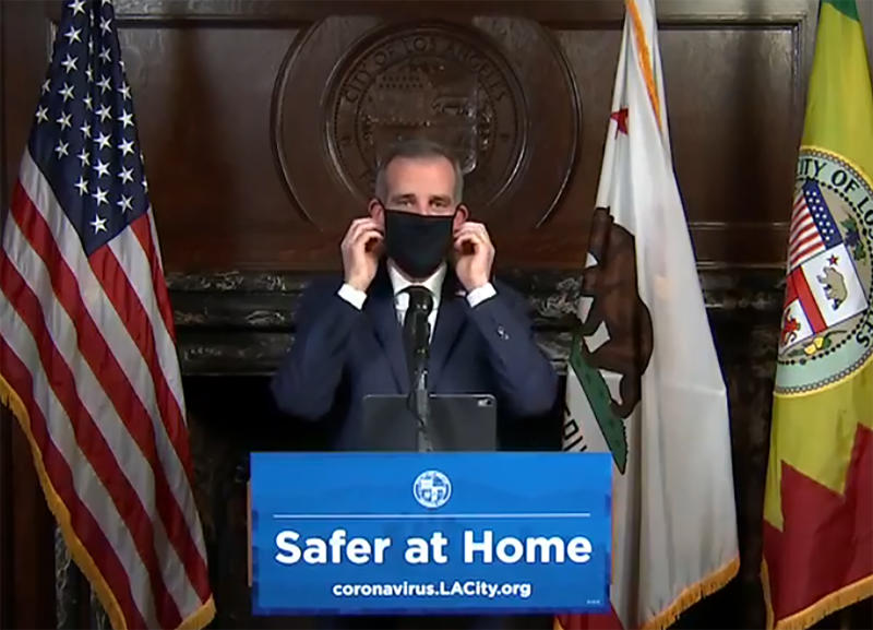 This still image taken from a live stream provided by Office of Mayor Eric Garcetti showing Los Angeles Mayor Garcetti displaying putting on a protective face mask during his daily news conference in Los Angeles on Wednesday, April 1, 2020. Garcetti has recommended that the city's 4 million people wear masks when going outside amid the spreading coronavirus. (Office of Mayor Eric Garcetti via AP)