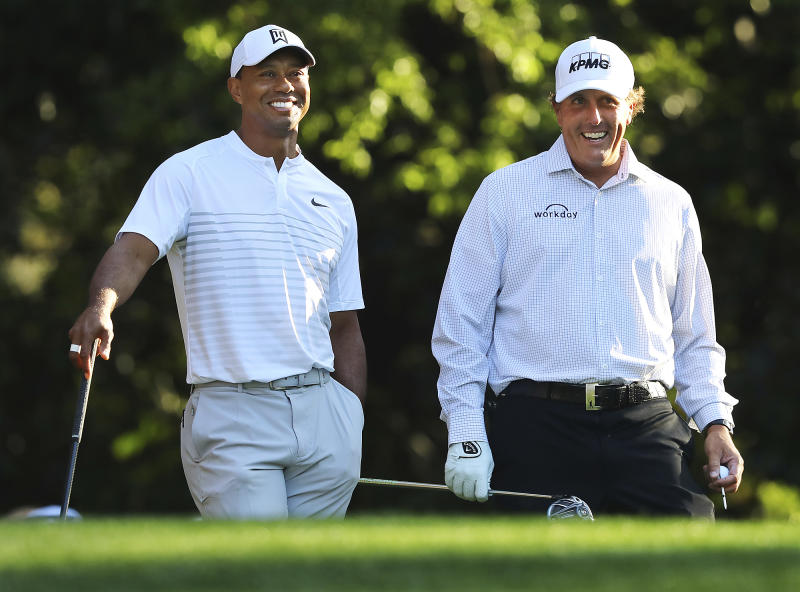 """FILE - In this April 3, 2018, file photo, Tiger Woods, left, and Phil Mickelson share a laugh on the 11th tee box while playing a practice round for the Masters golf tournament at Augusta National Golf Club in Augusta, Ga. The next match involving Tiger Woods and Phil Mickelson involves a $10 million donation for COVID-19 relief efforts, along with plenty of bragging rights in a star-powered foursome May 24 at Medalist Golf Club. Turner Sports announced more details Thursday, May 7, 2020, for """"The Match: Champions for Charity,"""" a televised match between Woods and Peyton Manning against Mickelson and Tom Brady. (Curtis Compton/Atlanta Journal-Constitution via AP, File)"""