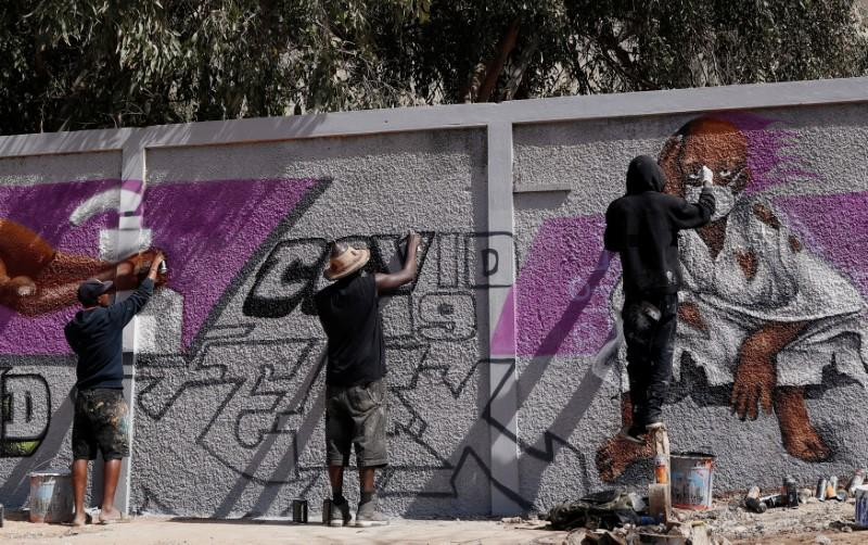 Graffiti artists from RBS crew work on their mural to encourage people to protect themselves amid the outbreak of the coronavirus disease (COVID-19), in Dakar