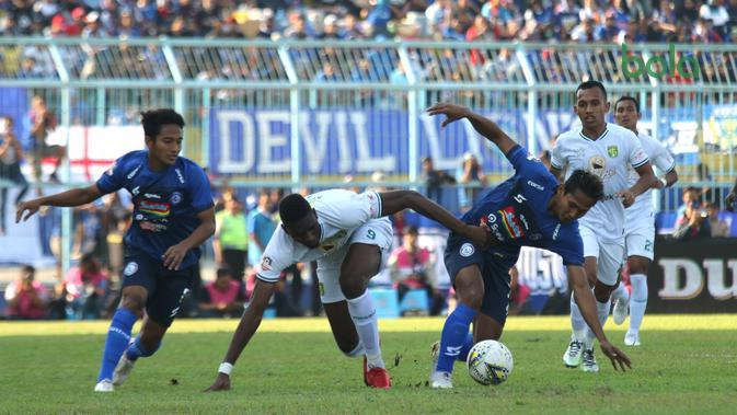 Striker Persebaya Surabaya, Amido Balde, berebut bola dengan pemain Arema, Hendro Siswanto, dalam laga pekan ke-14 Shopee Liga 1 2019 di Stadion Kanjuruhan, Malang, Kamis (15/8/2019). (Bola.com/Aditya Wany)