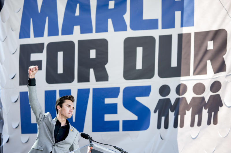 """FILE - In this March 24, 2018, file photo, David Hogg, a survivor of the mass shooting at Marjory Stoneman Douglas High School in Parkland, Fla., raises his fist after speaking during the March for Our Lives rally in support of gun control in Washington. Students from Marjory Stoneman Douglas High School who began speaking out for gun reform faced accusations that some were """"crisis actors"""" and the group was under the manipulation of gun control advocates. (AP Photo/Andrew Harnik, File)"""