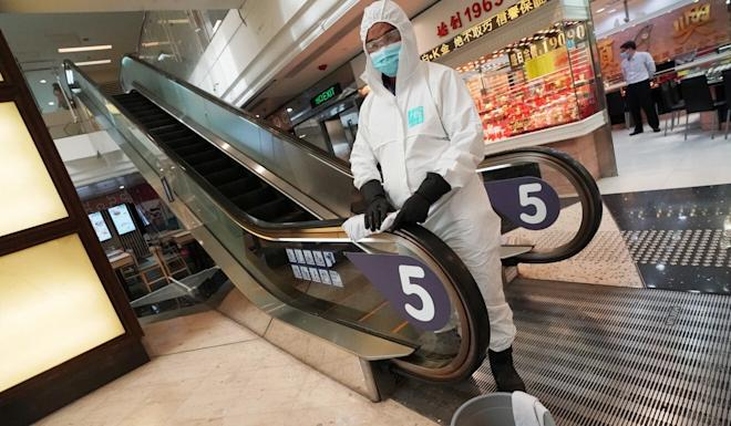 A worker in full protective wear disinfects an escalator handrail in Tsz Wan Shan. Photo: Felix Wong