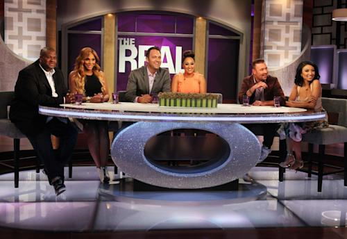 "This undated publicity photo released by Warner Bros. shows hosts Tamar Braxton, second left, with husband, Vincent Herbert, left, Tamera Mowry-Housley, center, with husband, Adam Housley, and Jeannie Mai, right, with husband Freddy Harteis, on the set of ""The Real."" The ladies of ""The Real"" discussed changing their last names after getting married and Braxton revealed she'll soon be known as Tamar Herbert during an episode, ""Bring Your Husband To Work Day."" ""The Real"" is taking a different approach to the TV talk show format with a younger, multi-ethnic panel. (AP Photo/Warner Bros., Michael Rozman)"