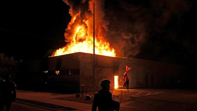 Bendera Amerika jatuh dari tiangnya saat polisi berusaha mengamankan daerah itu setelah pengunjuk rasa membakar gedung di Kenosha, Wisconsin, Amerika Serikat, Senin (24/8/2020). Protes dipicu oleh penembakan Jacob Blake oleh petugas polisi Kenosha sehari sebelumnya. (AP Photo/David Goldman)