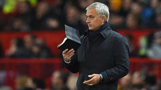 Pelatih Tottenham Hostpur, Jose Mourinho membawa buku saat pertandingan melawan Manchester United pada lanjutan Liga Inggris di Old Trafford, Rabu (4/12/2019). Mourinho gagal mengalahkan Manchester United mantan klub yang pernah dilatihnya. (AFP Photo/Oli Scarff)