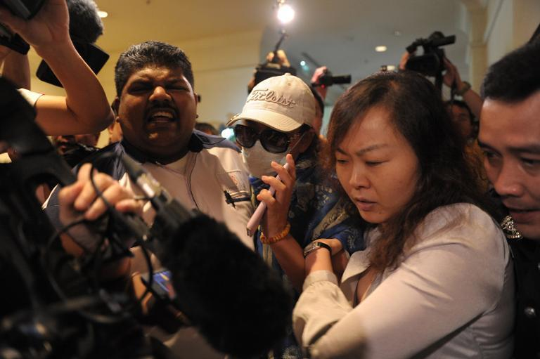 Chinese relatives of passengers from the missing Malaysia Airlines flight are stopped and escorted away by Malaysian police from entering a media centre at a hotel near Kuala Lumpur Airport on March 19, 2014