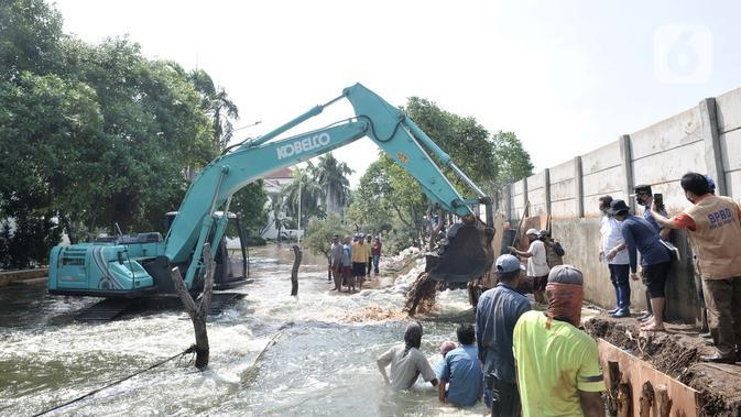 Pekerja menggunakan kendaraan alat berat saat menyelesaikan perbaikan tanggul jebol di Kompleks Perumahan Pantai Mutiara, Pluit, Jakarta, Minggu (7/6/2020). (Liputan6.com/Iqbal S. Nugroho)