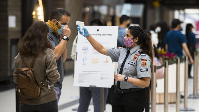 Petugas keamanan yang mengenakan masker memeriksa suhu tubuh seorang pelanggan di luar gerai Apple, Toronto, Kanada, 6 Oktober 2020. Hingga Selasa (6/10/2020) sore waktu setempat, Kanada melaporkan 170.945 kasus COVID-19 termasuk 9.527 kematian. (Xinhua/Zou Zheng)