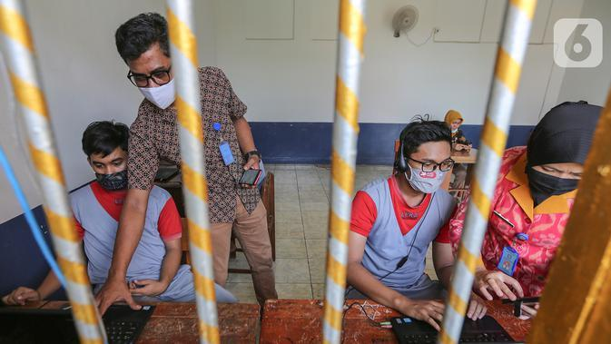 Anak binaan dibantu pegawai lapas anak tengah menyiapkan komunikasi virtual dengan keluarganya di Lembaga Pembinaan Khusus Anak (LPKA) Klas 1 Tangerang, Banten, Sabtu (30/5/2020). Kunjungan fisik diganti dengan komunikasi virtual selama pandemi Covid-19. (Liputan6.com/Fery Pradolo)