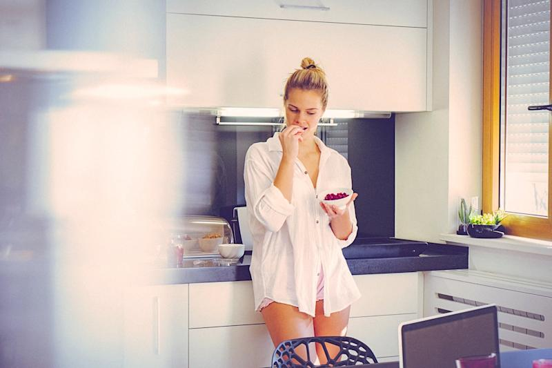 Attractive blonde woman in the morning, at home in the kitchen, eating pomegranate. The woman is dressed in pajamas and it seems that she recently got out of the bed and started to prepare breakfast. Her long blonde hair is swept back from her face. She seems sleepy. The shot is executed with available natural light, and the copy space has been left. Shallow DOF. Soft focused.