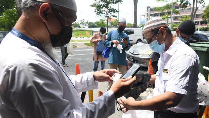 Petugas memeriksa pendaftaran umat muslim untuk salat Jumat usai pencabutan pembatasan Covid-19 di Masjid Al-Istighfar, Singapura, Jumat (26/6/2020). Masjid-masjid di Singapura menyediakan 2 sesi setiap Jumat dengan kuota yang diperbolehkan adalah 50 orang pada satu waktu. (Roslan RAHMAN/AFP)