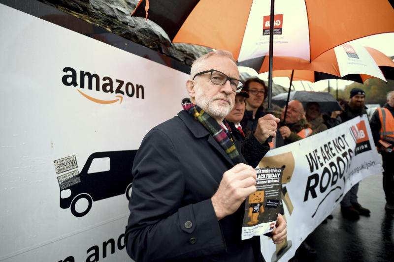Labour Party leader Jeremy Corbyn stands outside an Amazon depot to announce plans for a workers' rights revolution and to ensure big businesses pay their fair share of taxes, in Sheffield, England, Saturday Nov. 23, 2019. Britain goes to the polls on Dec. 12.  (Stefan Rousseau/PA via AP)