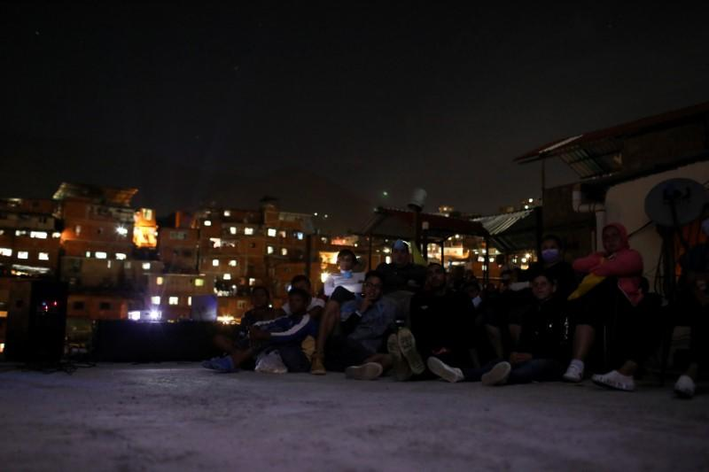 People sit on a roof to watch a movie projected on a giant screen in the low-income neighborhood of Petare, amid the coronavirus disease (COVID-19) outbreak in Caracas