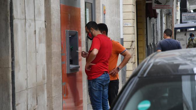 Orang-orang yang mengenakan masker menarik uang di sebuah mesin ATM di Tunis, Tunisia, pada 5 Oktober 2020. Perdana Menteri Tunisia Hichem Mechichi pada 3 Oktober mengumumkan serangkaian langkah untuk membatasi penyebaran cepat COVID-19 di negara tersebut. (Xinhua/Adel Ezzine)