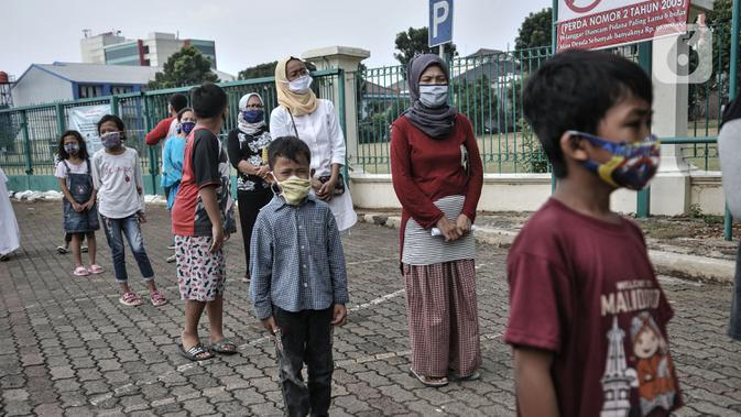 Anak-anak didampingi orang tua berbaris dengan standar protokol kesehatan saat antre menerima donasi ponsel yang diberikan Komunitas #WartawanLintasMedia saat acara #PonselPintarUntukPelajar di Jakarta, Minggu (9/8/2020). (merdeka.com/Iqbal S. Nugroho)
