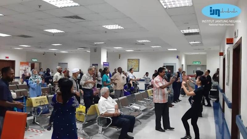 Outpatients engaging in simple exercises to pass the time in IJN's waiting room. — Picture via Facebook/IJN.Malaysia