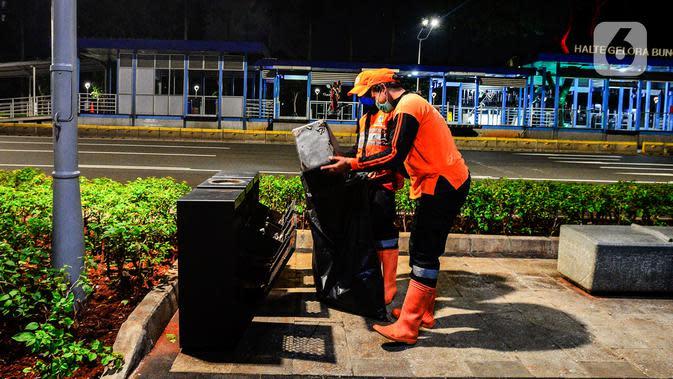 Pasukan oranye mengumpulkan sampah di tengah Pandemi Covid-19, Jakarta, Jumat (8/5/2020). Semenjak diberlakukan Pembatasan Sosial Berskala Besar (PSBB) yang diterapkan Ibu Kota membuat aktivitas warga berkurang dan jalan menjadi lengang. (merdeka.com/Imam Buhori)